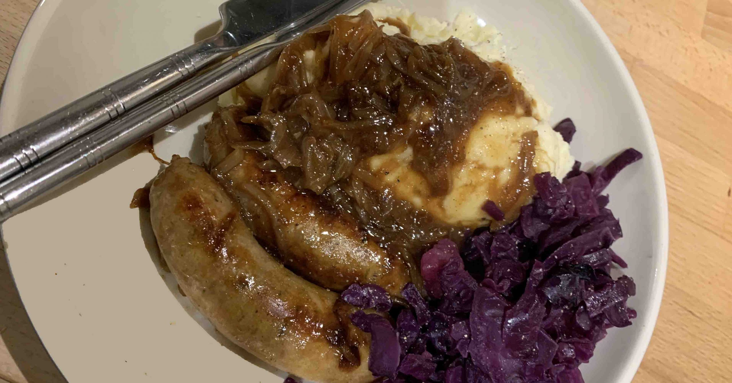 Sausages, onion gravy, mashed potato and stewed cabbage